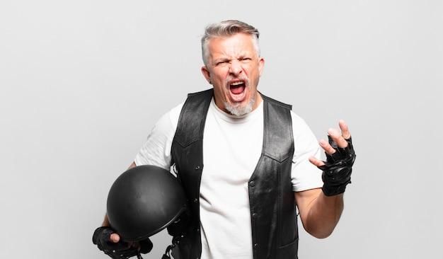 Motocycliste senior à la colère, agacé et frustré qui crie wtf ou qu'est-ce qui ne va pas avec vous