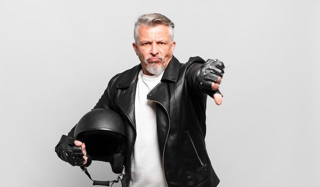Motocycliste senior se sentant fâché, en colère, agacé, déçu ou mécontent, montrant les pouces vers le bas avec un regard sérieux