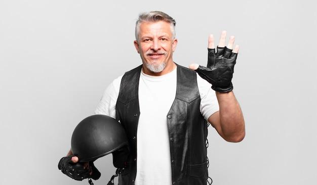 Motocycliste senior souriant et semblant sympathique, montrant le numéro cinq ou cinquième avec la main en avant, compte à rebours