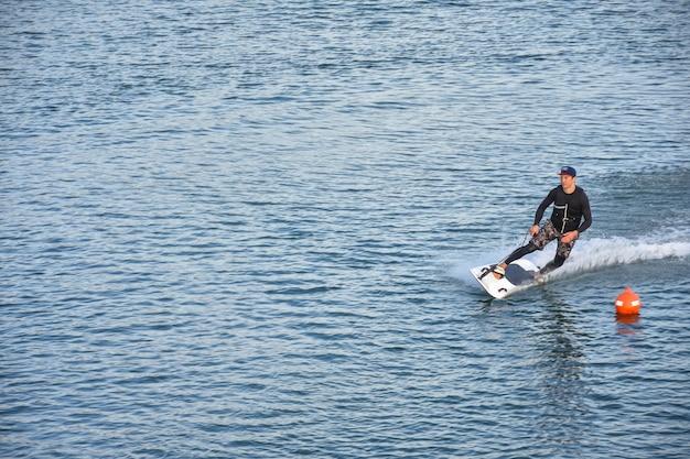 Motosurf concurrent prenant un virage à grande vitesse faisant beaucoup de jet. jet surf sur l'eau, homme à cheval sur une planche de jet surf. surfer en mouvement, sport d'été