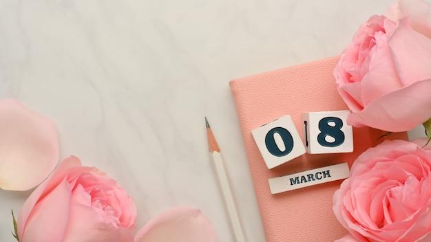 Dés avec les mots «08 mars» sur le livre de journal sur une table en marbre décorée de fleurs roses et espace copie