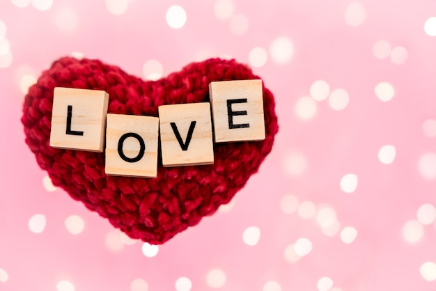 Les mots aiment sur un coeur en peluche rouge flou fond rose avec copie-espace avec bokeh d'une guirlande dorée et des lumières.
