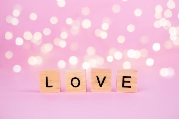 Mots d'amour sur un fond rose flou avec un beau bokeh d'une guirlande d'or et de lumières.