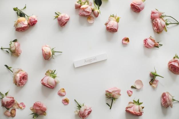 Mots d'août sur bloc de bois et roses sur fond blanc