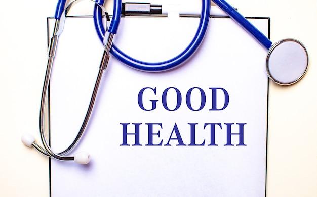 Les mots bonne santé sont écrits sur une feuille blanche près du stéthoscope