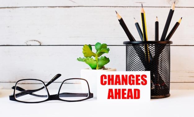Les mots changements à venir écrits sur une carte de visite blanche à côté de crayons dans un support et des verres. a proximité se trouve une plante en pot
