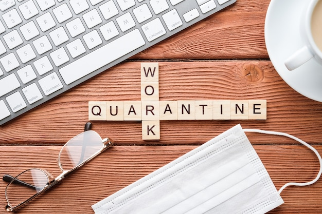 Mots croisés sur un thème médical, ordinateur, téléphone et café sur une table en bois. concept de quarantaine pandémique