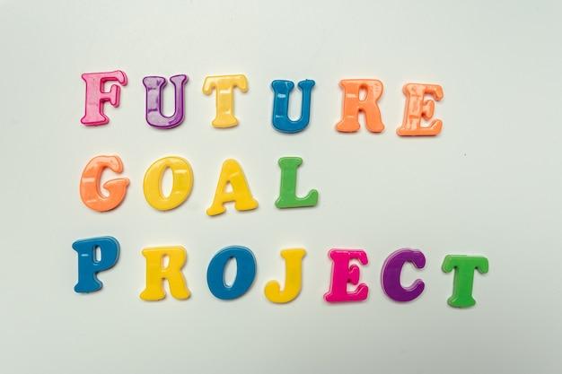 Mots du projet d'objectif futur écrits en lettres colorées en plastique sur fond blanc