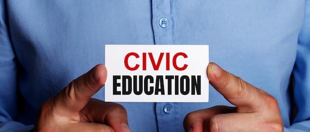 Les mots éducation civique sont écrits sur une carte de visite blanche entre les mains d'un homme. concept d'entreprise