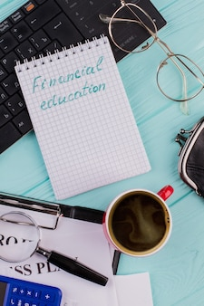 Mots d'éducation financière sur le bloc-notes, le clavier et la tasse de café sur le bureau bleu clair. diverses fournitures de bureau se composent d'un presse-papiers de loupe de calculatrice.