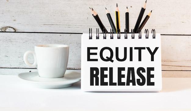Les mots equity release sont écrits dans un bloc-notes blanc près d'une tasse de café blanc sur fond clair