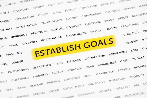 Les mots «établir des objectifs» sont mis en évidence avec un marqueur sur papier. concept d'entreprise, stratégie, planification, succès