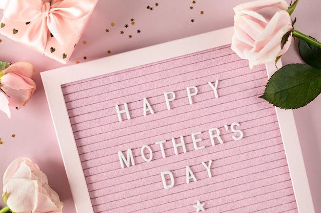 Mots de fête des mères heureux sur carton à lettres en feutre rose composition festive avec des roses et une boîte avec un cadeau sur une surface rose. vue de dessus, mise à plat. copiez l'espace.