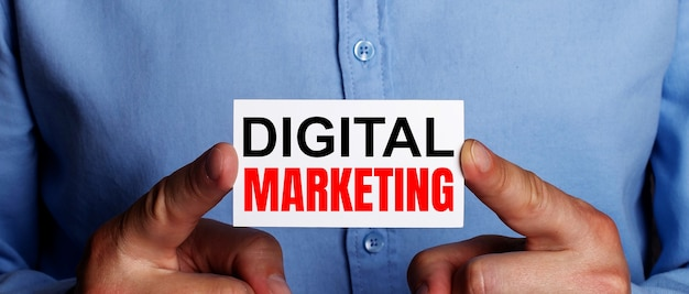 Les mots marketing numérique sont écrits sur une carte de visite blanche entre les mains d'un homme