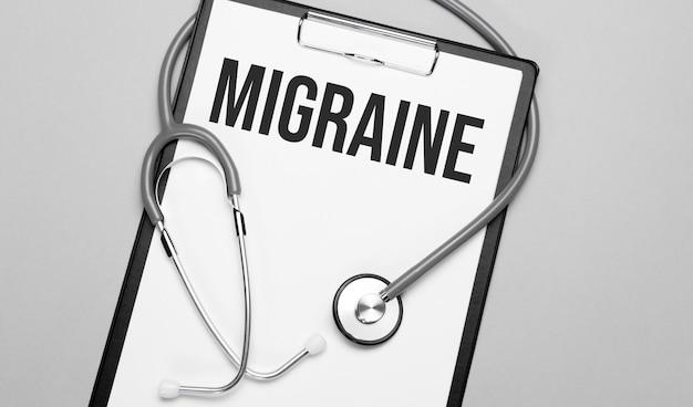 Les mots migraine sont écrits sur du papier blanc sur fond gris près d'un stéthoscope.