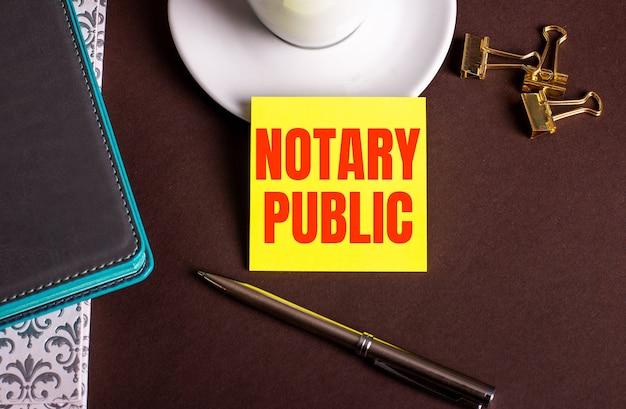 Les mots notaire public écrits sur papier jaune sur fond marron près d'une tasse de café et d'agendas