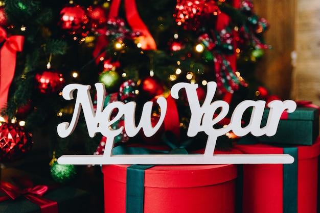 Mots nouvel an avec des cadeaux de noël en arrière-plan