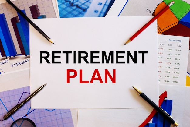 Les mots plan de retraite sont écrits sur une surface blanche à proximité de graphiques colorés, de stylos et de crayons
