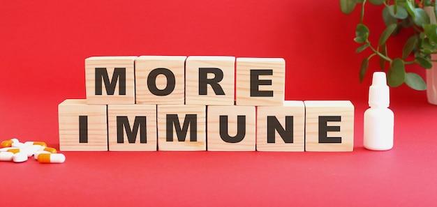 Les mots plus immunités sont constitués de cubes en bois sur une table rouge avec des médicaments. concept médical.