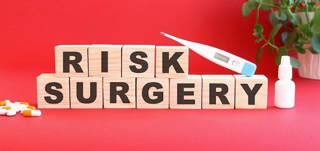Les mots risk surgery sont constitués de cubes en bois sur fond rouge. notion médicale.