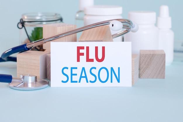Mots de saison de la grippe écrits sur une carte médicale blanche, avec stéthoscope, fleur verte, pilules médicales et blocs de bois