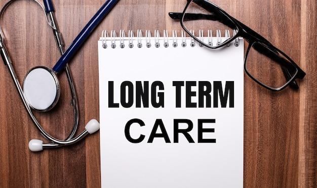 Les mots soins à long terme sont écrits sur du papier blanc sur une surface en bois près d'un stéthoscope et de lunettes à monture noire