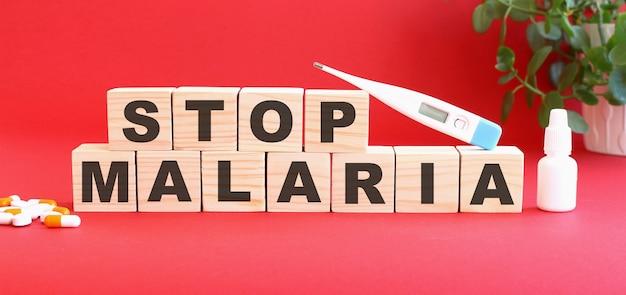 Les mots stop malaria sont constitués de cubes en bois sur une table rouge. concept médical.