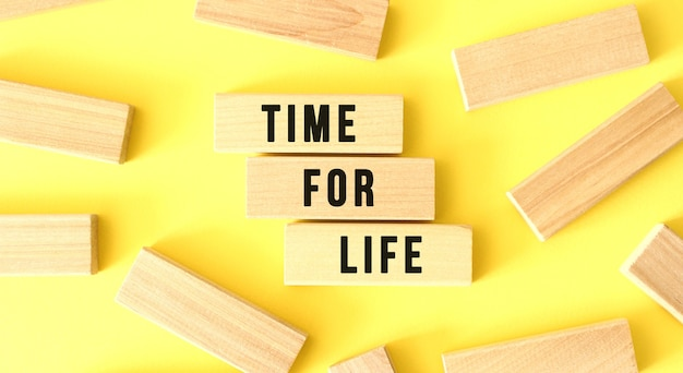 Les mots time for life sont écrits sur des blocs de bois éparpillés sur fond jaune. concept d'entreprise