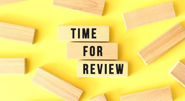 Les mots time for review sont écrits sur des blocs de bois éparpillés sur fond jaune. concept d'entreprise