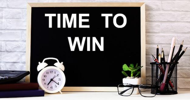Les mots time to win sont écrits sur le tableau à côté du réveil blanc, des verres, des plantes en pot et des crayons dans un support