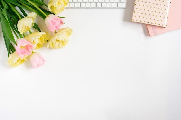 Mouche plate de printemps avec des cahiers à clavier bouquet de tulipes roses sur fond clair