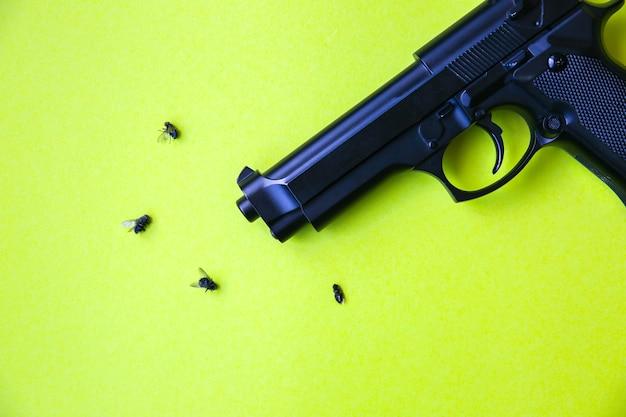 Des mouches mortes posées sur la table près du pistolet. idée de concept répulsif.