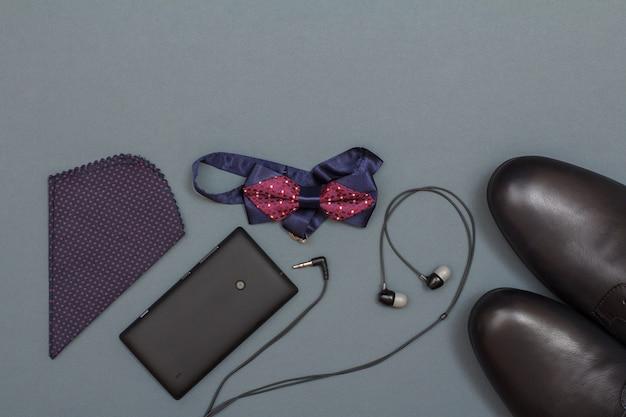 Mouchoir, téléphone portable, casque, nœud papillon et chaussures pour hommes noirs sur fond gris. accessoires pour hommes. vue de dessus avec espace de copie