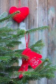 Moufles tricotées en laine de chameau de couleur rouge ornée de strass rouges, cœurs de lapins sur la branche d'un sapin de noël sur fond de vieilles planches et jouets de noël en forme de coeur