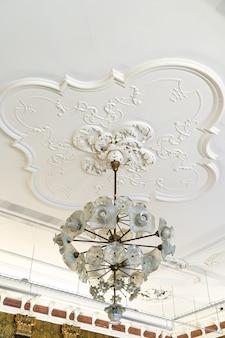 Moulage en relief en stuc d'argile décorative vintage antique ronde avec ornements floraux sur plafond blanc dans un intérieur de style classique abstrait