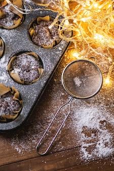 Moule de cuisson avec un savoureux muffins au chocolat sur la table en bois