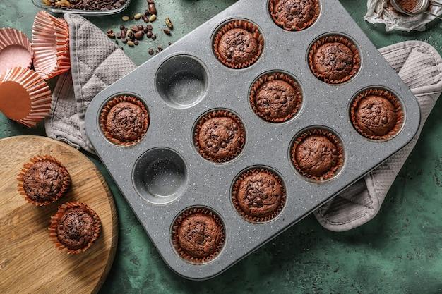 Moule de cuisson avec de savoureux muffins au chocolat sur la table