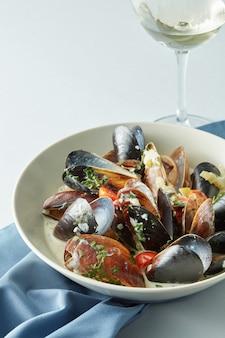 Moule avec sauce au vin blanc et verre de vin sur table