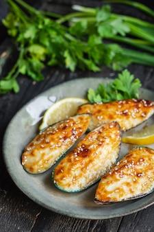 Moules au four au fromage à la crème sauce repas de fruits de mer collation sur la table copie espace arrière-plan alimentaire rustique