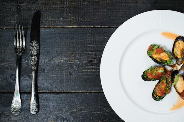 Moules au four à la sauce tomate avec coriandre et parmesan sur une assiette blanche.