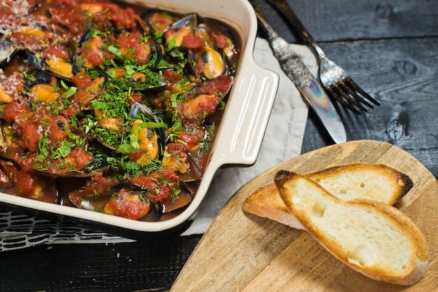 Moules au four à la sauce tomate avec coriandre et parmesan.