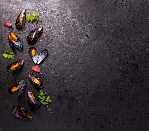 Moules bouillies aux épices sur un espace sombre avec copie espace
