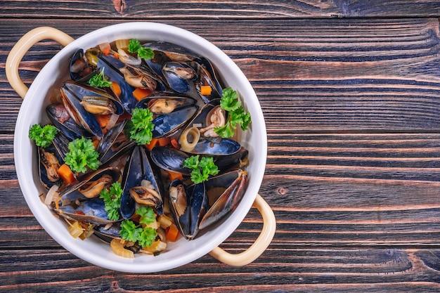 Moules bouillies dans un plat de cuisson avec du persil sur un fond en bois