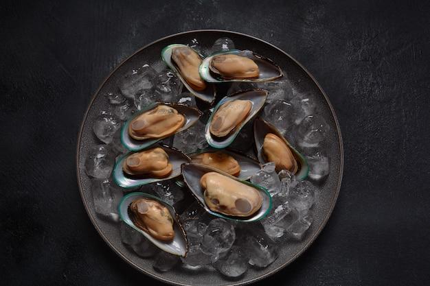 Moules crues de fruits de mer dans une assiette sur des glaçons