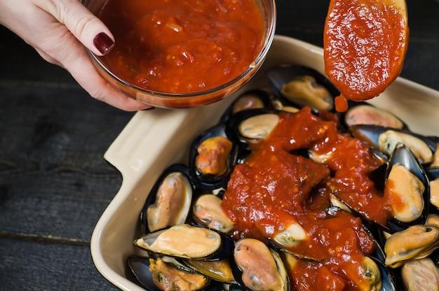 Moules crues à la pâte de tomates, cuisson.