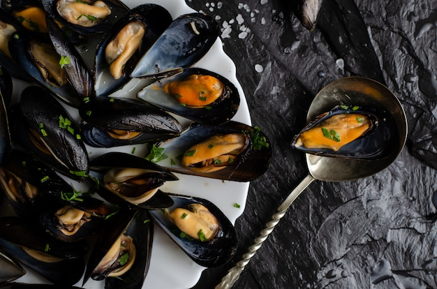 Moules cuites à la vapeur avec du persil. concept de cuisine méditerranéenne. vue de dessus, plat poser