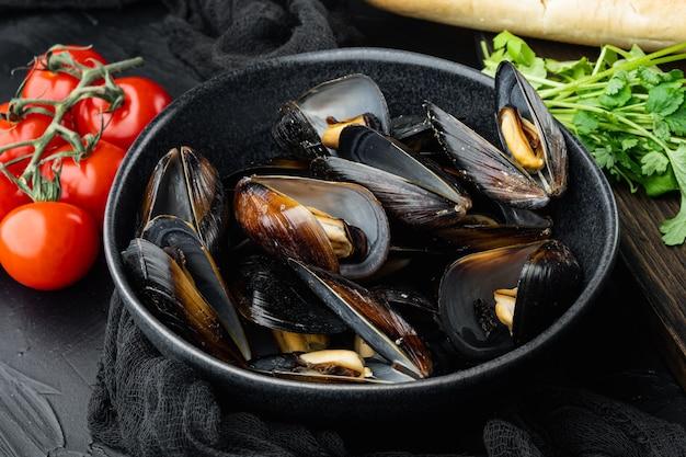 Moules cuites à la vapeur traditionnelles classiques dans un vin blanc en coquilles, dans un bol, sur fond noir