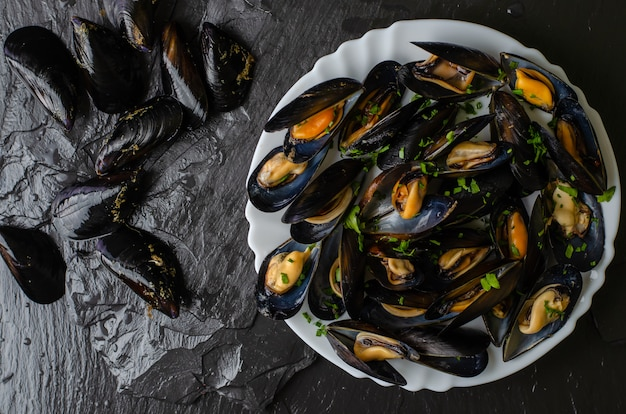 Moules fraîches crues et cuites sur fond de pierre ardoise noire. concept de fruits de mer. vue de dessus