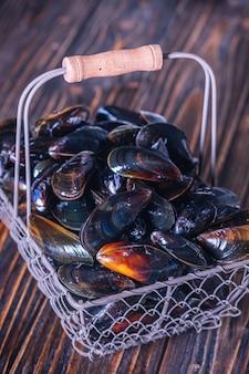 Moules fraîches dans un panier sur une planche de bois. fruit de mer.