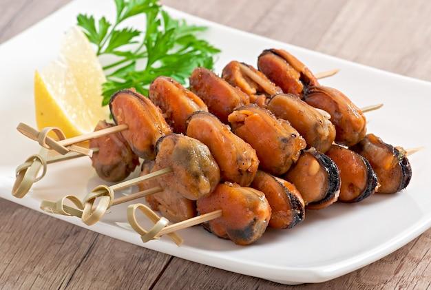 Moules frites aux oignons sur des brochettes c garniture de haricots verts et paprika